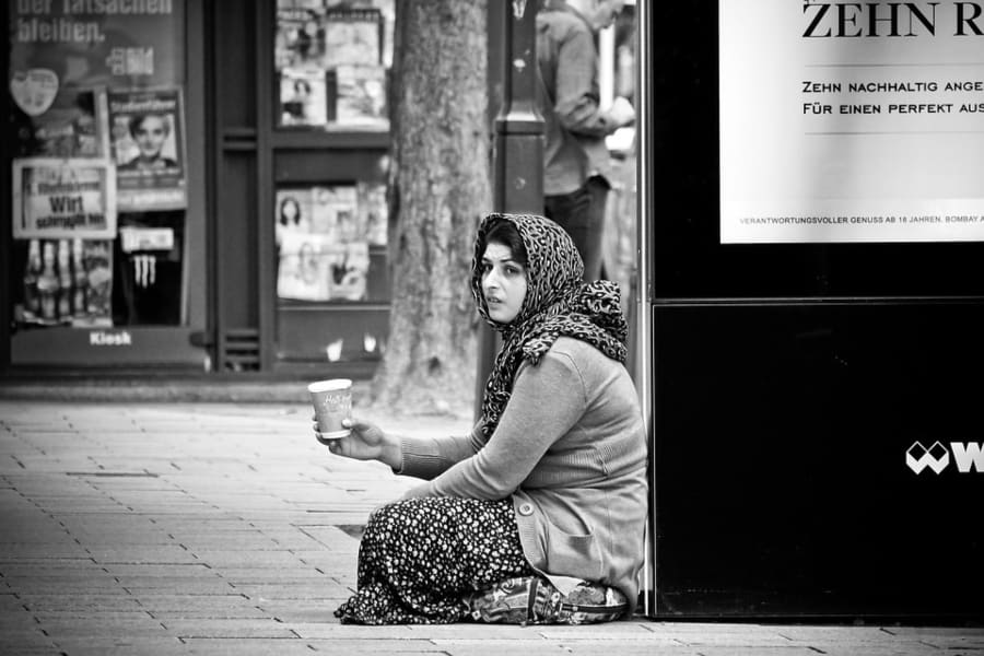 street photograph of a woman sitting on the side of the road