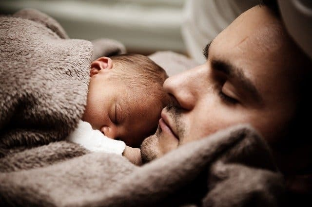 parent with baby sleeping