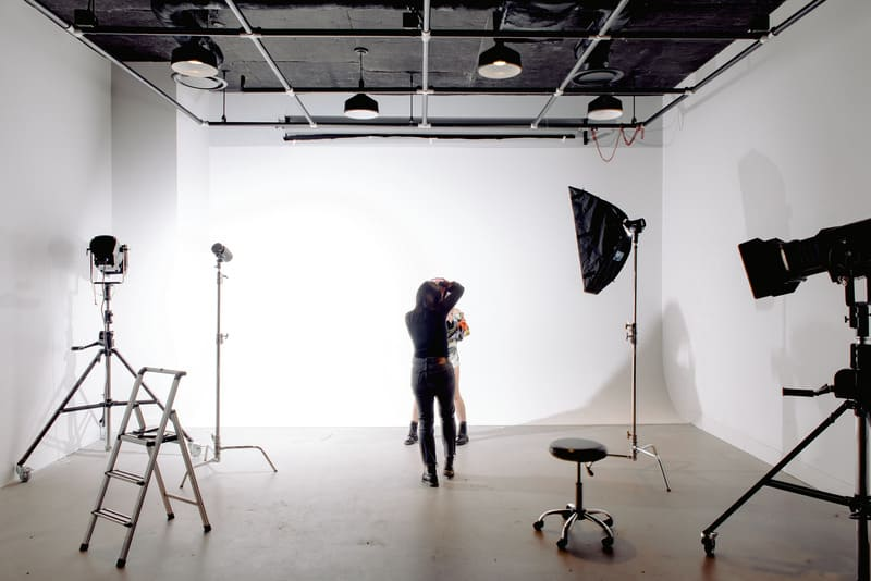 photographer standing in photo studio with speedlights and strobes set up