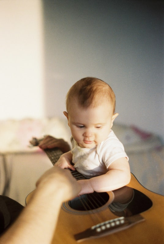 baby holding guitar