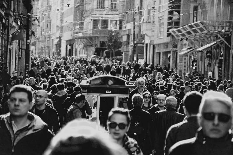 black and white image of people walking on crowded city sidewalk