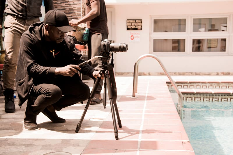 man setting up camera by a pool