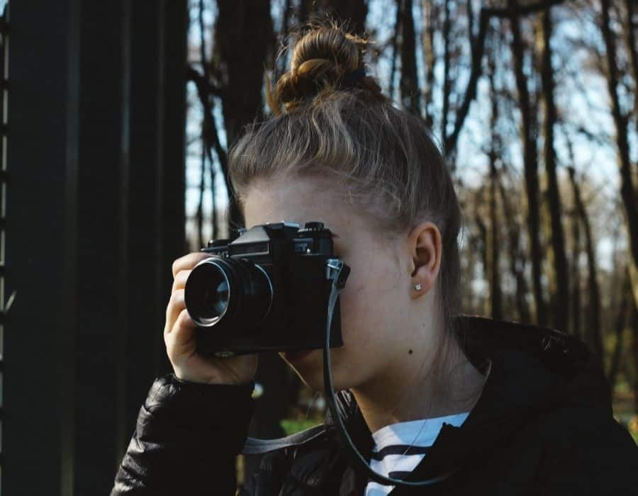 woman taking picture in the woods