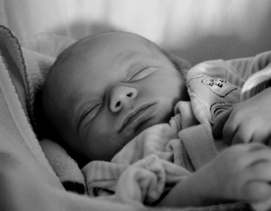 closeup of baby sleeping in black and white