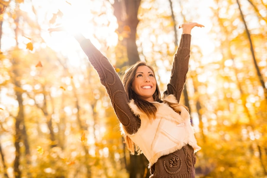 woman standing with arms upstretched in woods