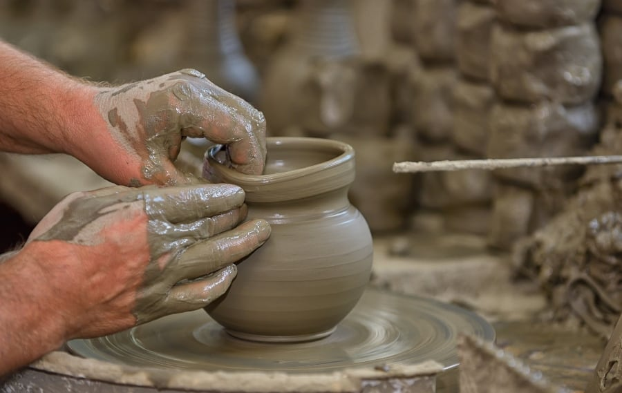 vase being formed on pottery wheel