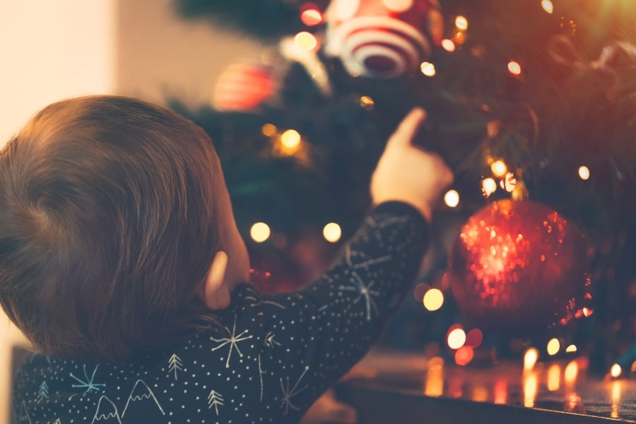 baby pointing at christmas tree ornaments