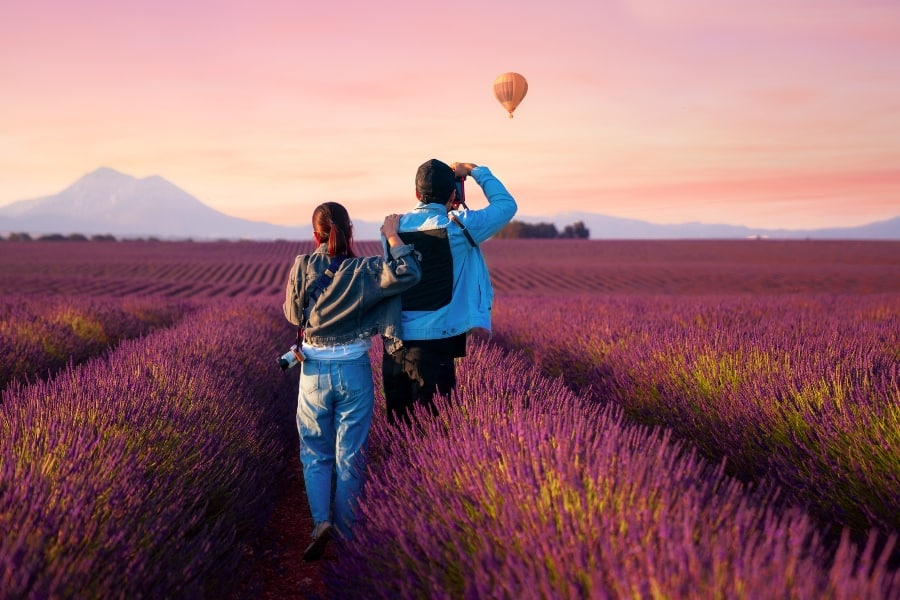 couple taking picture of hot air balloon with 35mm camera