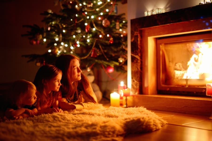family laying by fireplace