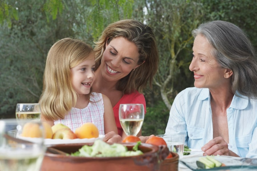 grandmother mother and daughter sitting at table smiling