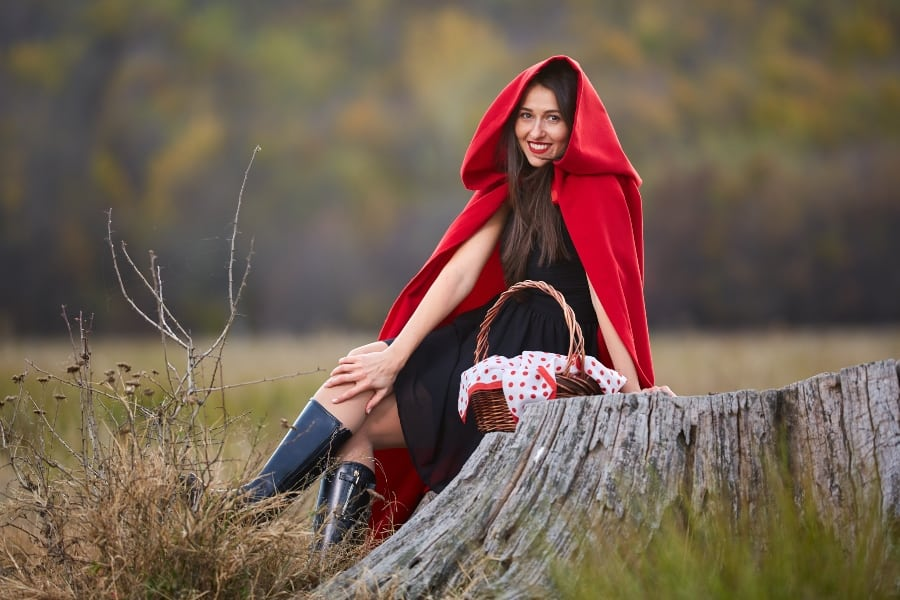 little red riding hood cosplayer sitting on stump