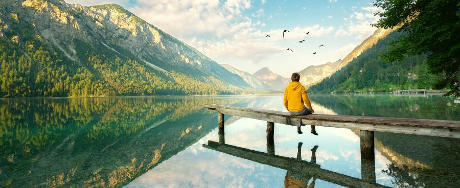 man sitting dock mountains in background