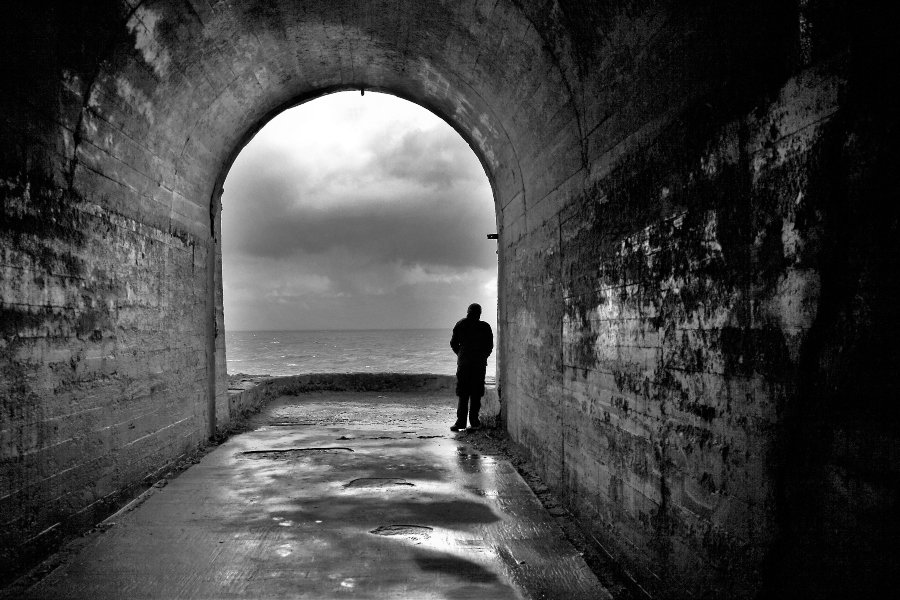 man standing in tunnel black and white image
