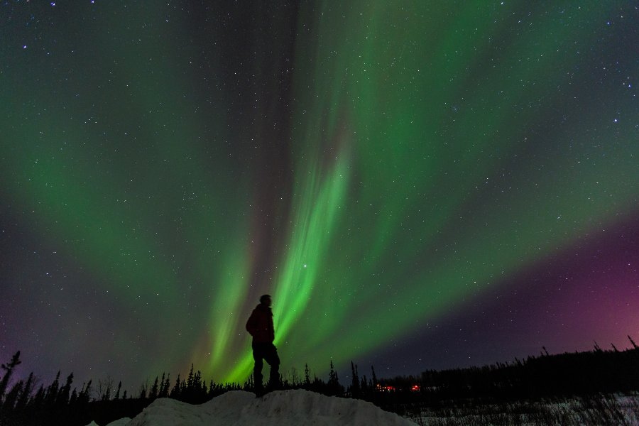 man standing with northern lights above him