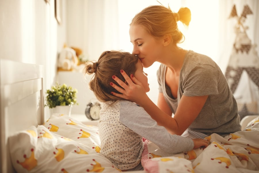 mother giving daughter a kiss