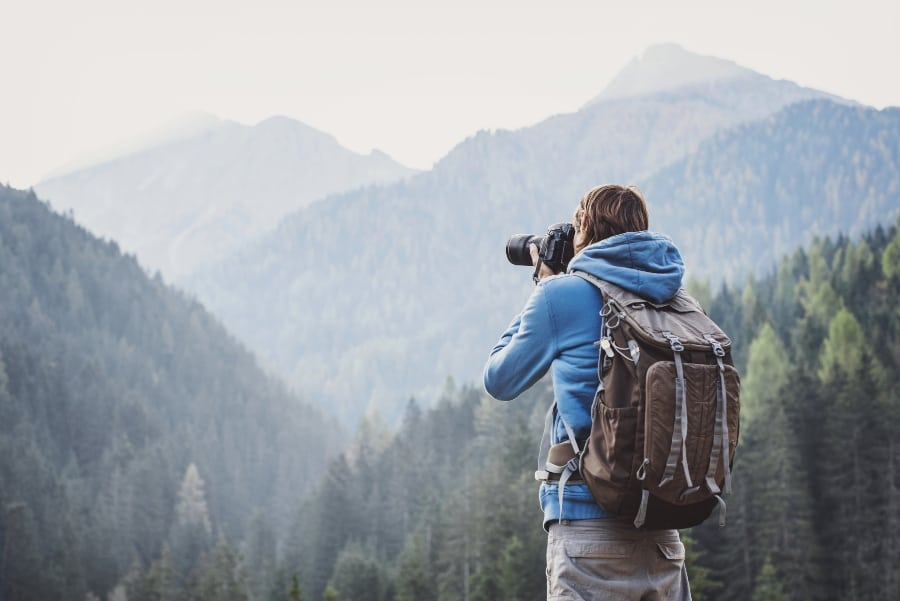 photographer taking picture of mountains