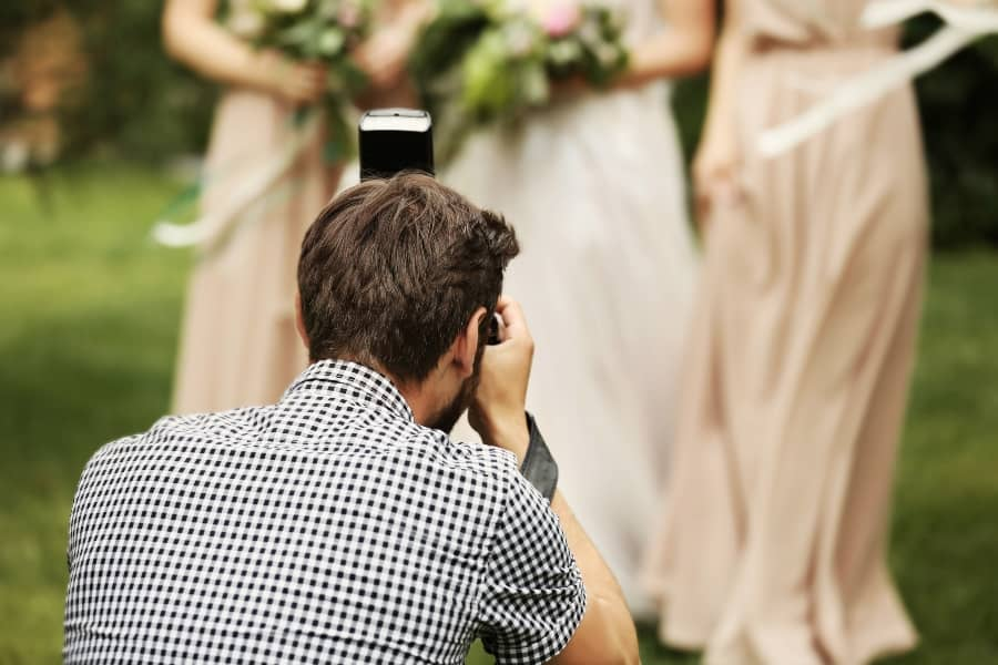 wedding photographer taking picture of wedding party