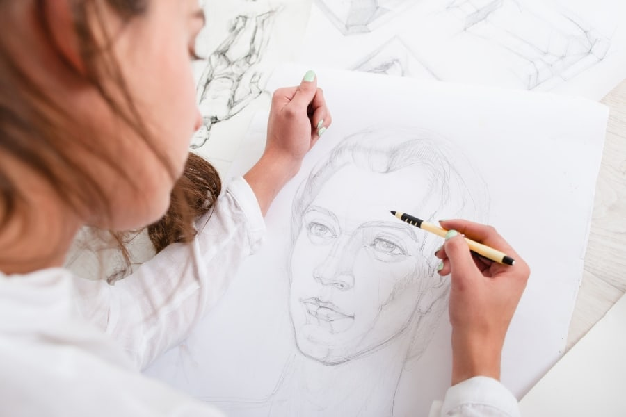 woman drawing a face on paper