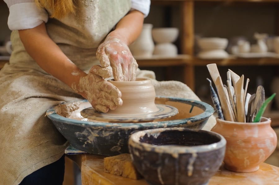 woman throwing clay on pottery wheel