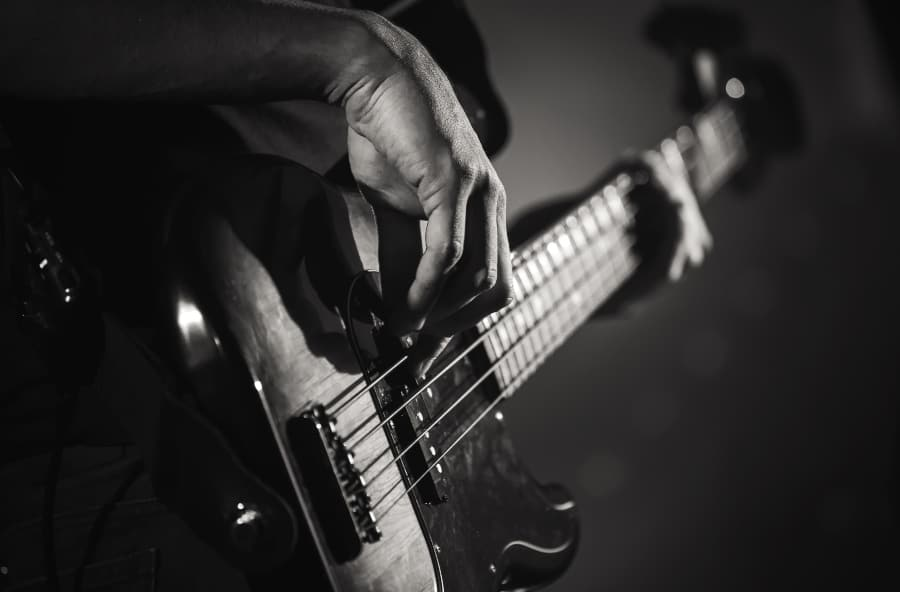 black and white photo of man playing bass guitar