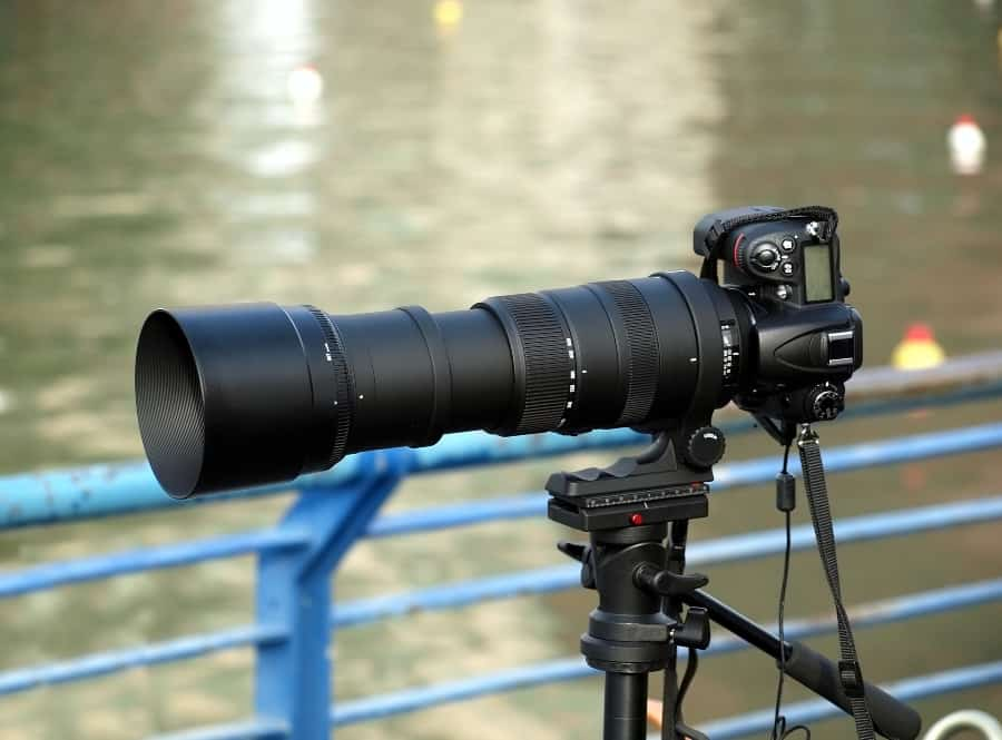 camera on tripod with telephoto lens