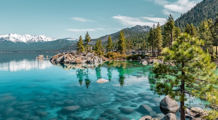 crystal clear lake surrounded by trees and mountains
