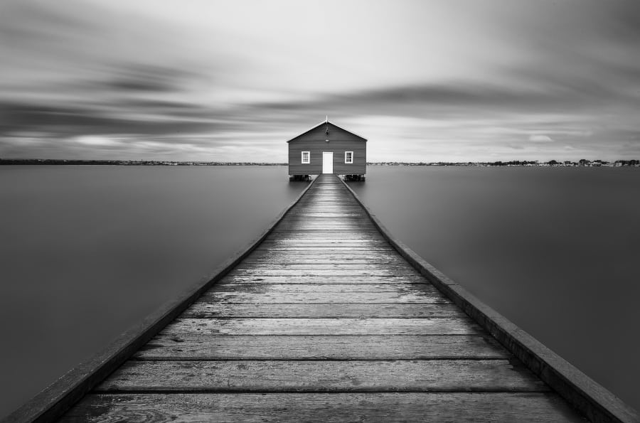 house in middle of lake with wooden dock in black and white
