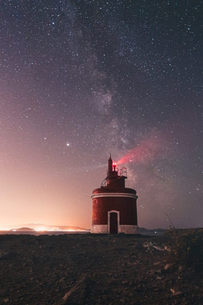 lighthouse with milky way above