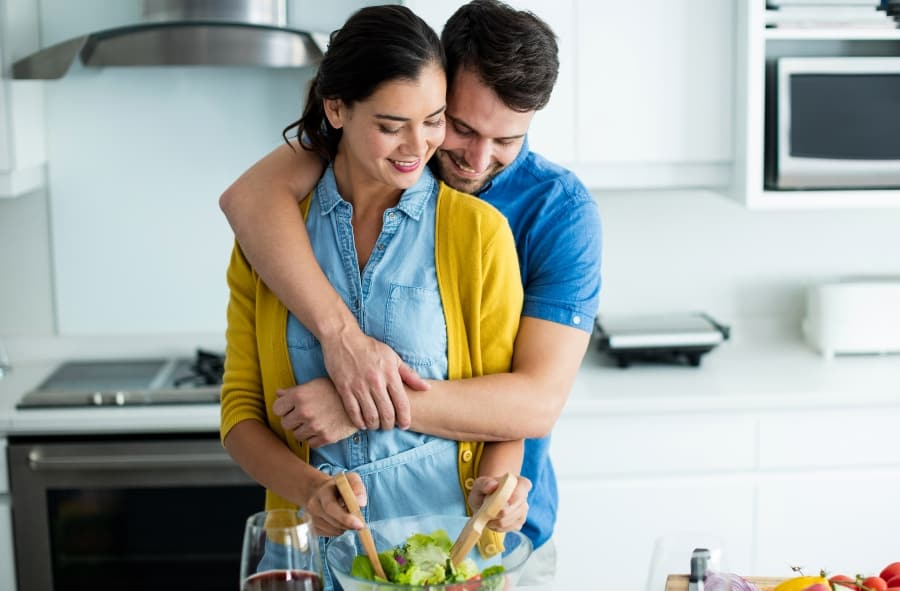 man embracing woman in kitchen