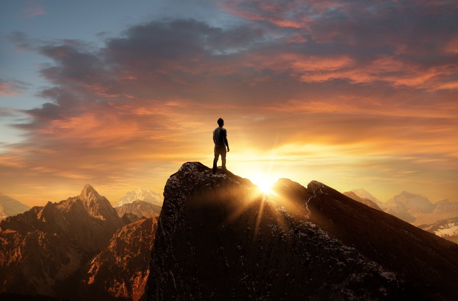 man standing on rock silhouette of mountains