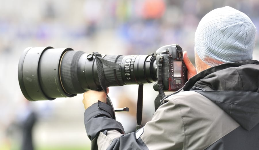 sports photographer on field with camera