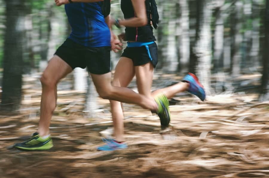 two cross country runners running in the forest